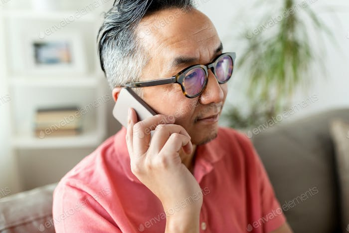 close up of asian man calling on smartphone