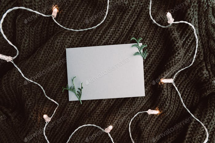 Top view on blank envelope on a warm sweater surrounded festoon lights
