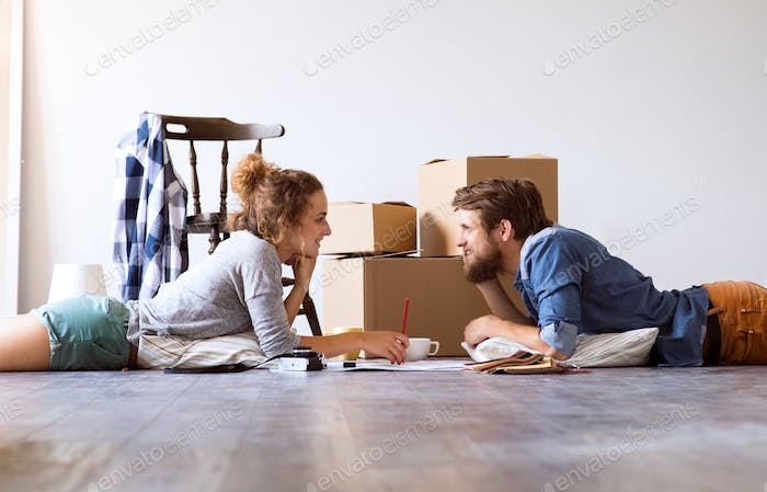 Young couple moving in new house, lying on the floor.