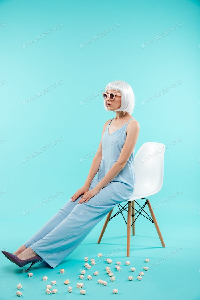 Full length of beautiful woman in sunglasses sitting on chair