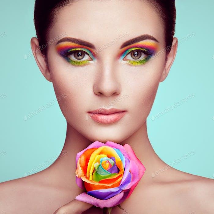 Porträt von schönen jungen Frau mit Regenbogenrose