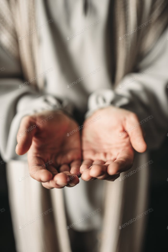 Man in white robe reaching out his hands