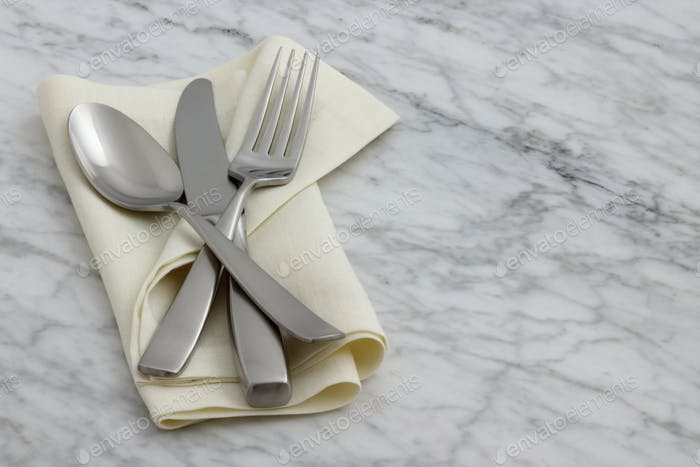 silverware and hemstitch napkin on antique carrara marble