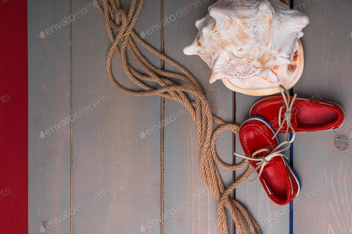 Red boat shoes near big shell and rope on wooden background. Top view/. Copy space. Frame.