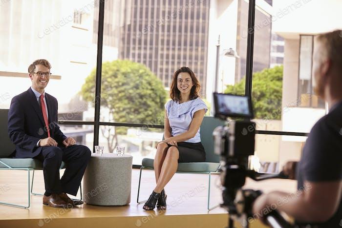Klug gekleideter Mann und Frau am Set für ein TV-Interview