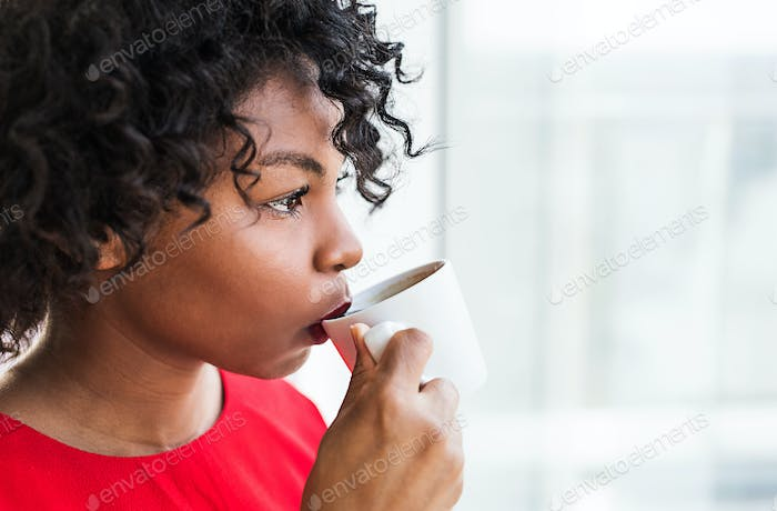 A close-up of a woman standing by the window drinking coffee.