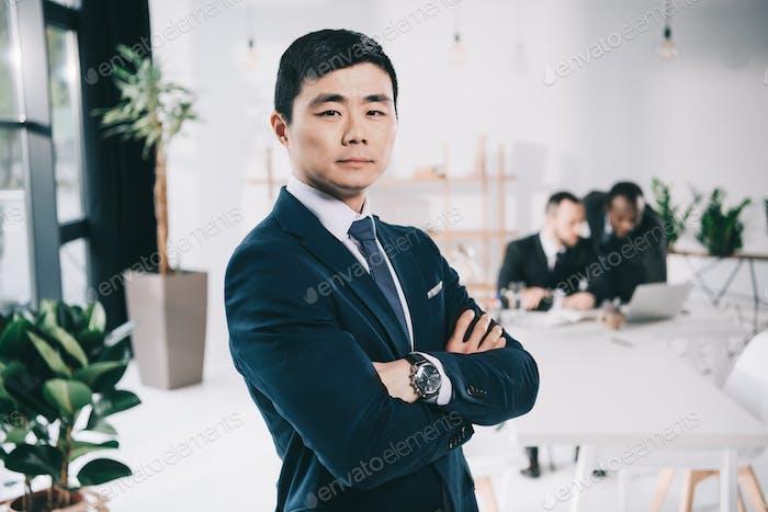 hübscher junger asiatischer Geschäftsmann mit gefalteten Armen