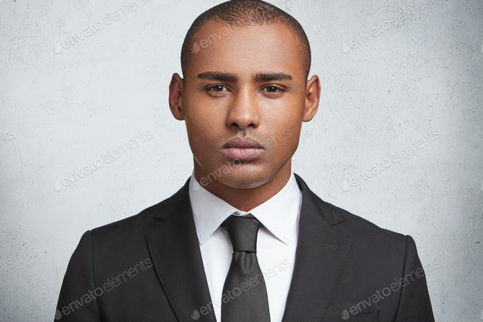 Serious male executive director or enterpreneur wears tie and black elegant suit, going to have busi