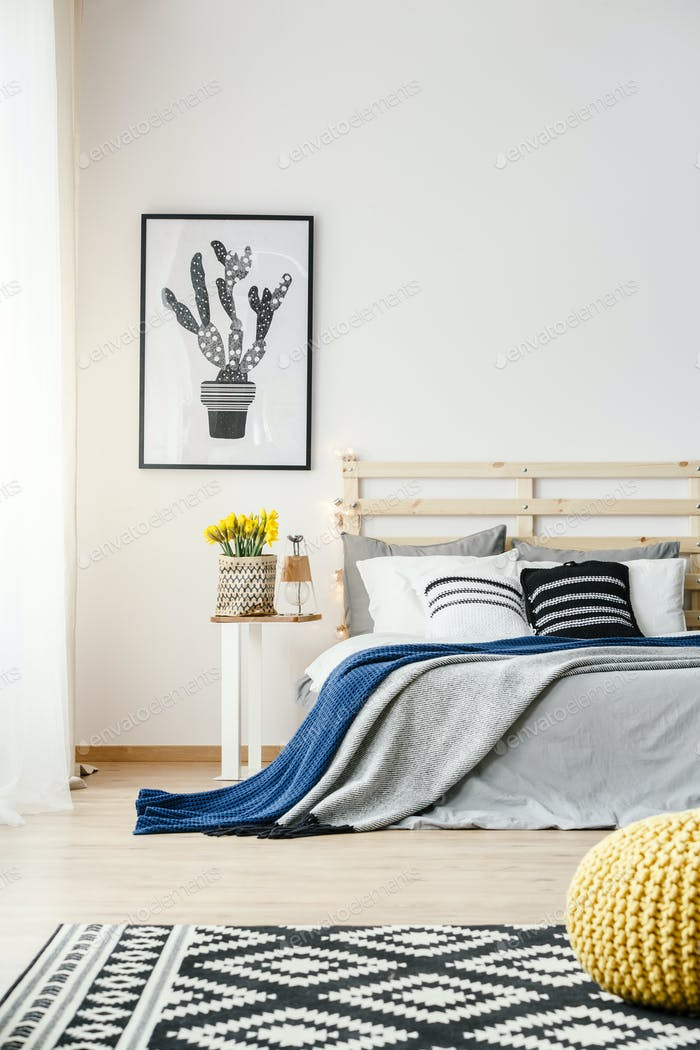 Black and white cactus poster hanging on the wall in bright bedr