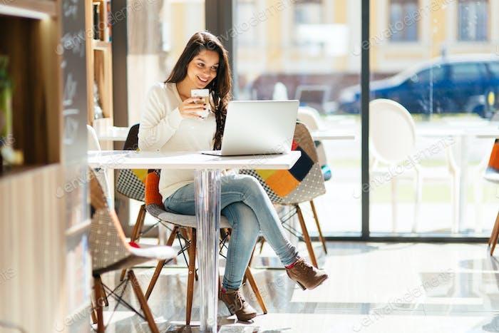 Beautiful brunette enjoying coffee and working
