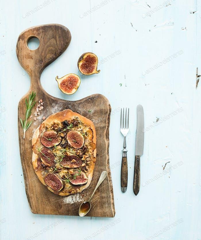 Rustic homemade pizza with figs, prosciutto and mozzarella cheese