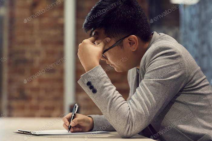 Young Asian Man Filling Form in Business Office