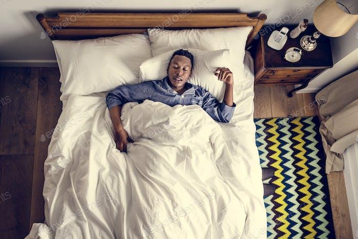 Schwarzer Mann schlafen auf Bett