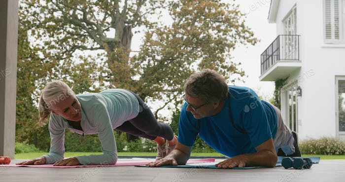 Side view of determined active senior Caucasian couple doing plank exercise in the porch at home