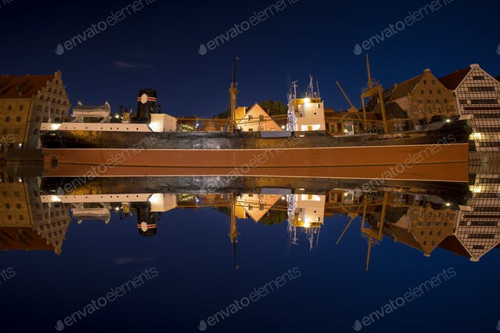 Reflections of the ship Soldek at night in the river Motlawa in Gdansk