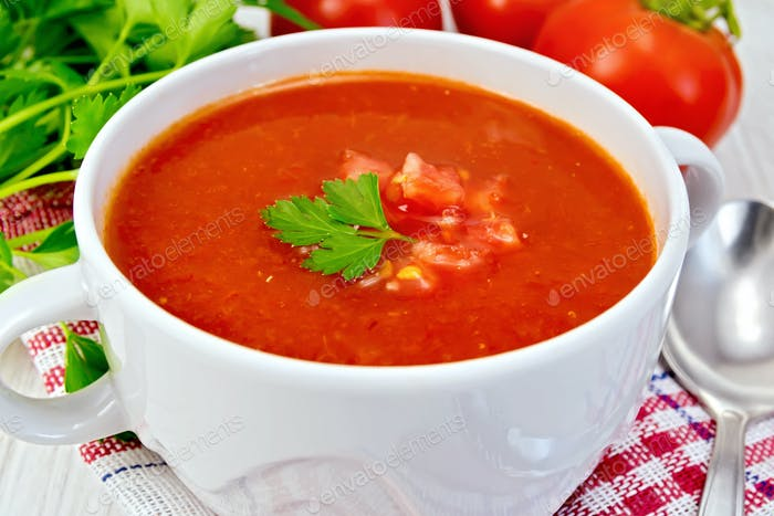 Soup tomato with spoon on napkin and board