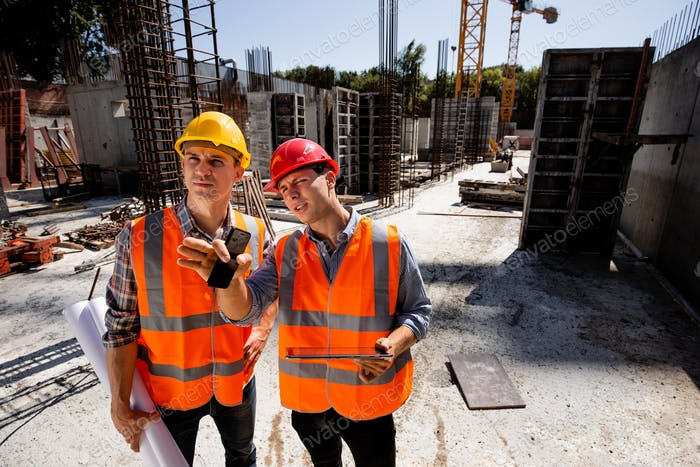 Structural engineer and architect dressed in orange work vests and hard bats discuss the