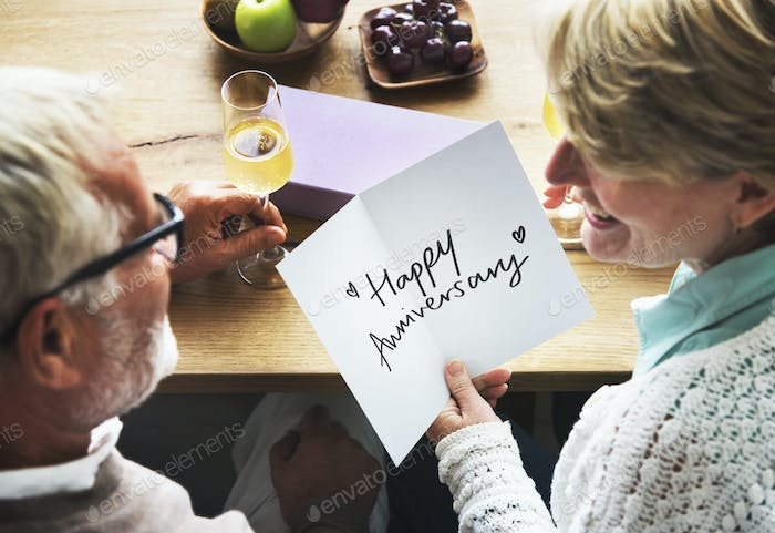 Mature couple holding an anniversary card