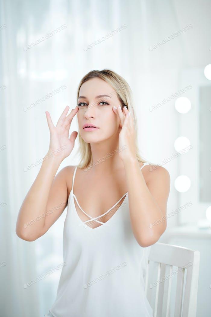 Woman applying eyes cream