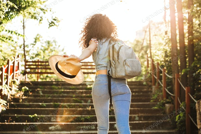 Photo from back of teenage woman 18-20 wearing summer clothes an