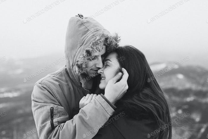 Teenager couple kissing hooded. Winter casual style, parka with fur hood