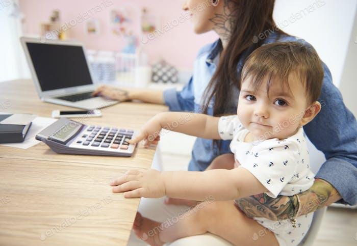 Baby Junge sitzt auf dem Mumien Schoß