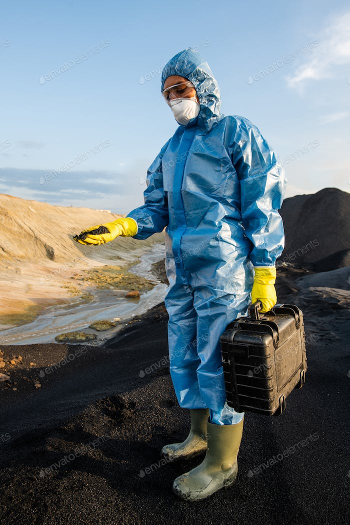 Young female ecologist in protective workwear holding briefcase with samples
