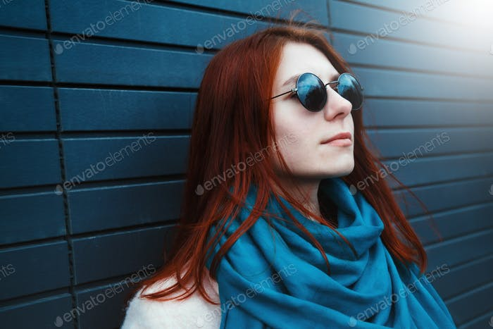 Red haired beautiful girl  in a pink coat and blue scarf, with sunglasses