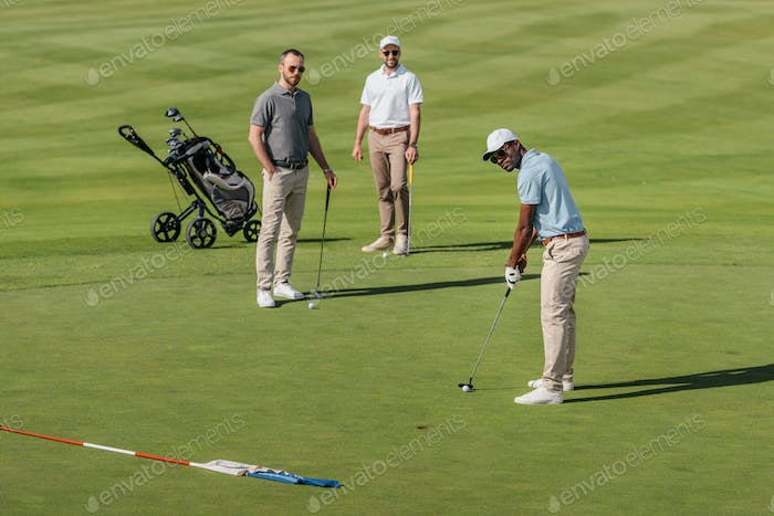 african american golfer take a shot with golf club while his friends standing behind on green