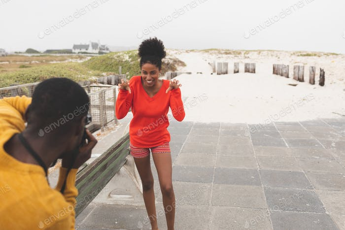 Man capturing photo of beautiful woman while standing at pavement