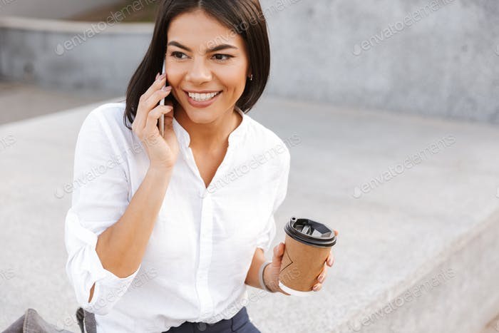 Cheerful business woman sitting outdoors with cup of coffee