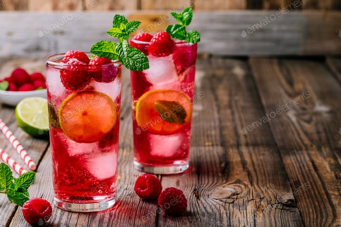 Raspberry Mojito Lemonade with lime and fresh mint in glass on wooden background