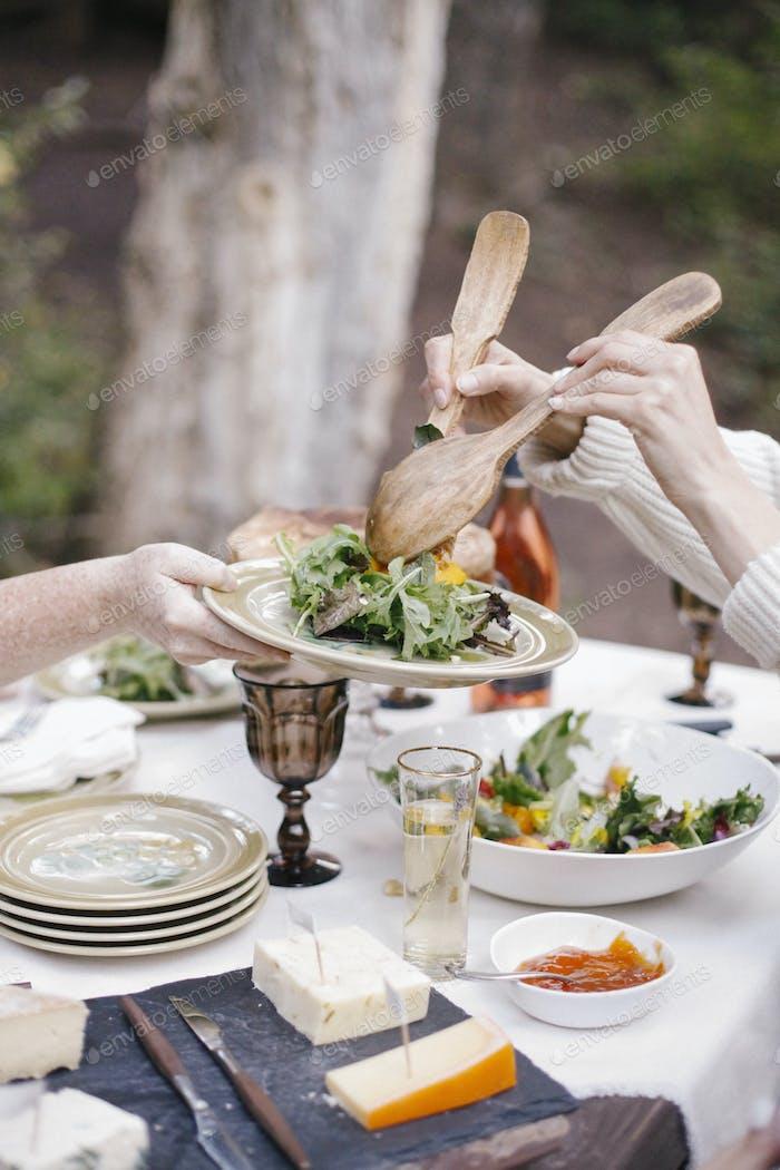 Eine Frau, die Salat auf einem Teller serviert.