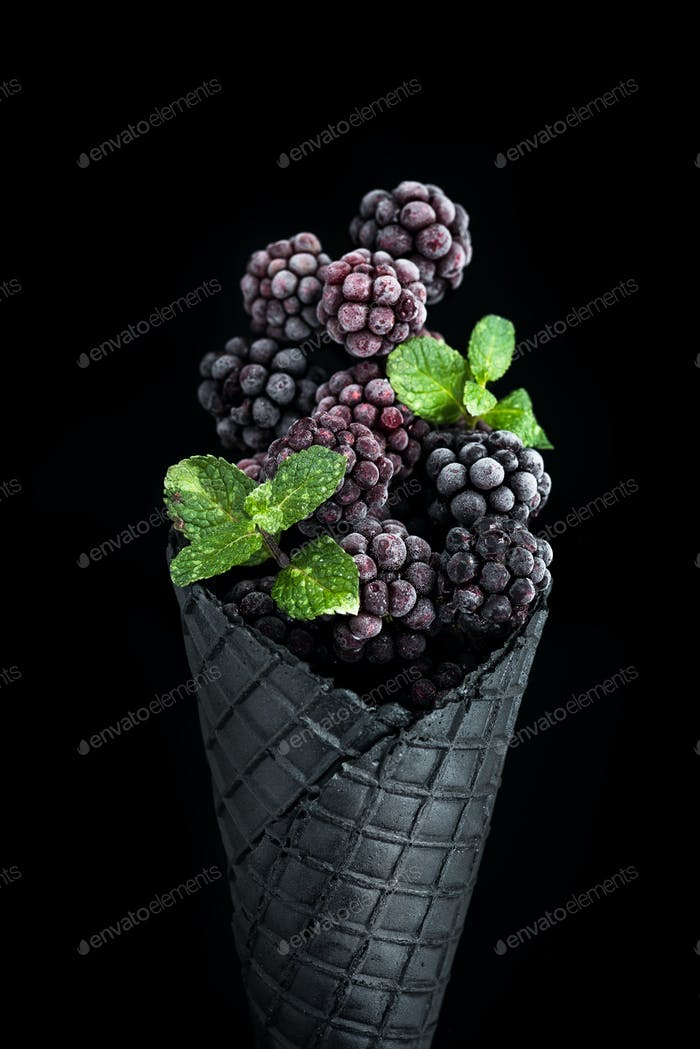 Black wafer cone with frozen blackberry fruits. Ice cream