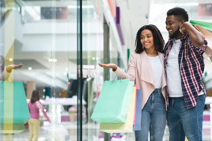 Discount Prices. Smiling Black Couple Shopping In Mall Together, Pointing At Showcase