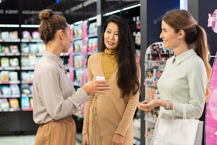 Young consultant of beauty supermarket recommending facial cream to clients