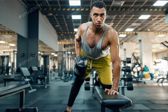 Athlete doing exercise with dumbbells on the bench