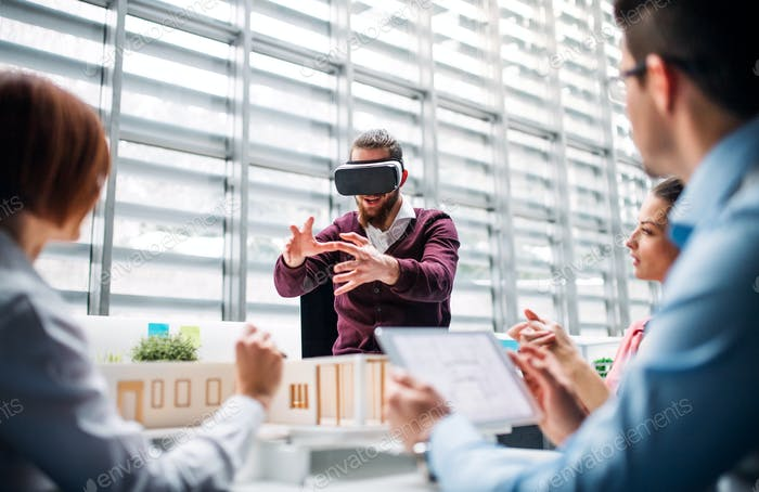 Group of young architects with model of a house and VR goggles working in office.