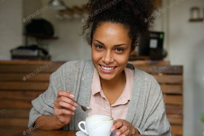Happy young african american woman with cup of coffee