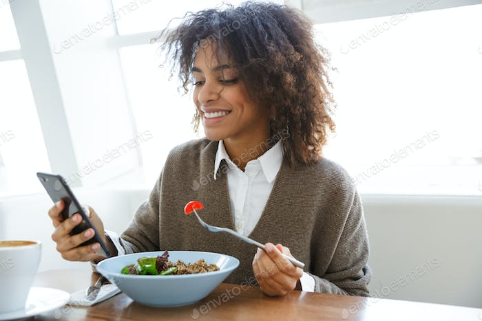 Portrait of african american woman using cellphone during lunch in cafe