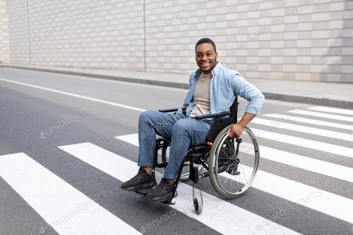 Quality of life and impairment concept. Positive disabled black guy in wheelchair crossing city