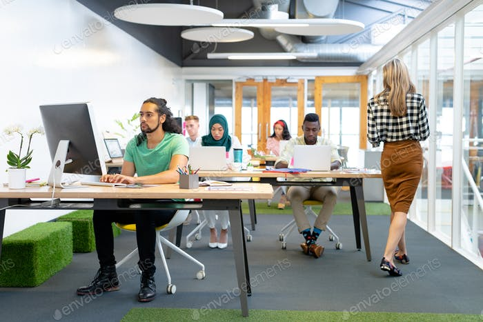 Front view of diverse business people working at desk in a modern office