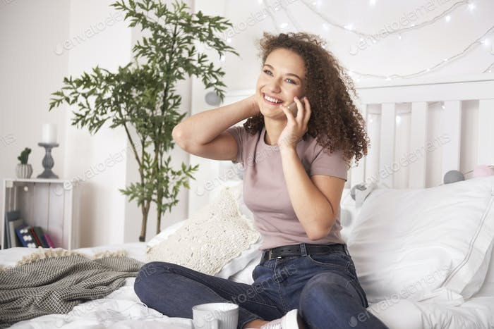 Happy teenage girl is on the phone