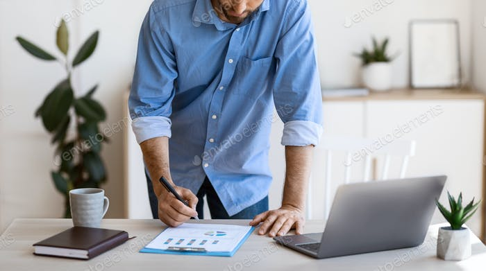 Businessman taking notes to financial report, working with documents at office, cropped