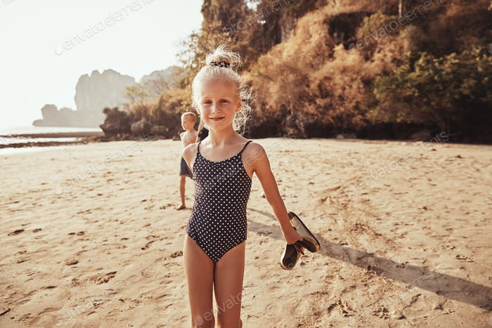 Smiling little girl walking with her family along a beach