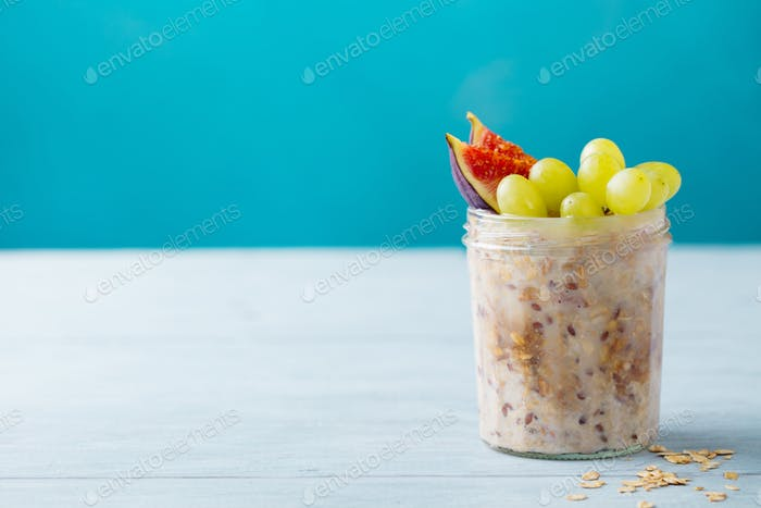 Overnight oats, bircher muesli with grape and figs. Blue background. Copy space