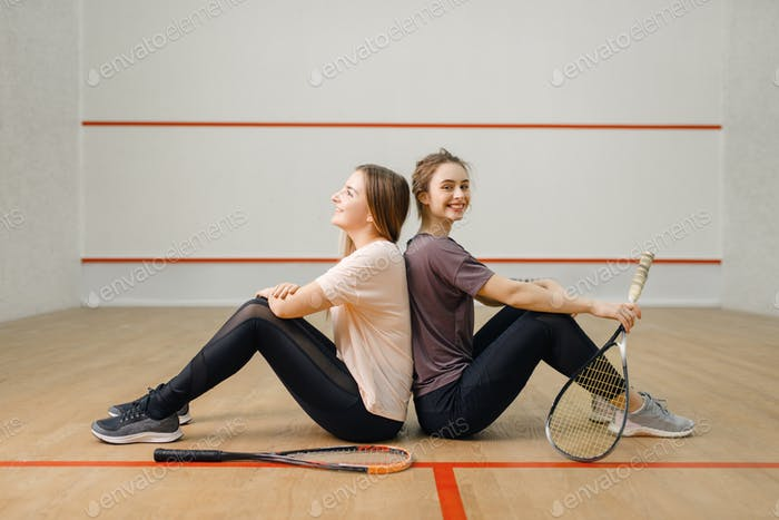 Players with squash rackets sits back to back