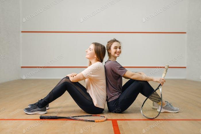 Spieler mit Squashschlägern sitzt zurück an Rücken