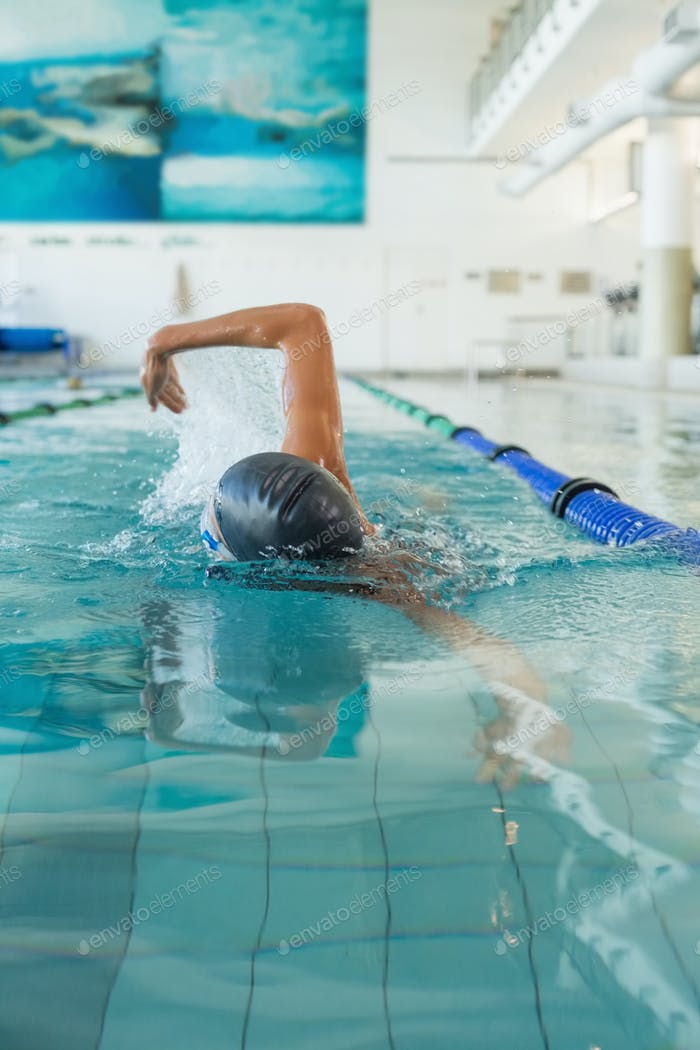 Fit swimmer doing the front stroke in the swimming pool at the leisure center