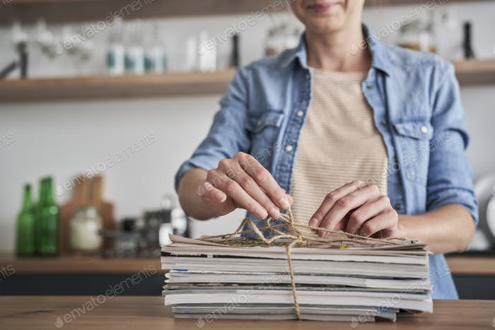 Woman preparing old newspapers for recycling